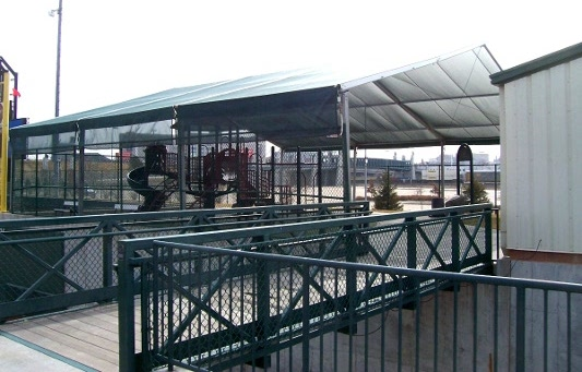 Image of a shade structure over slides at ball park.